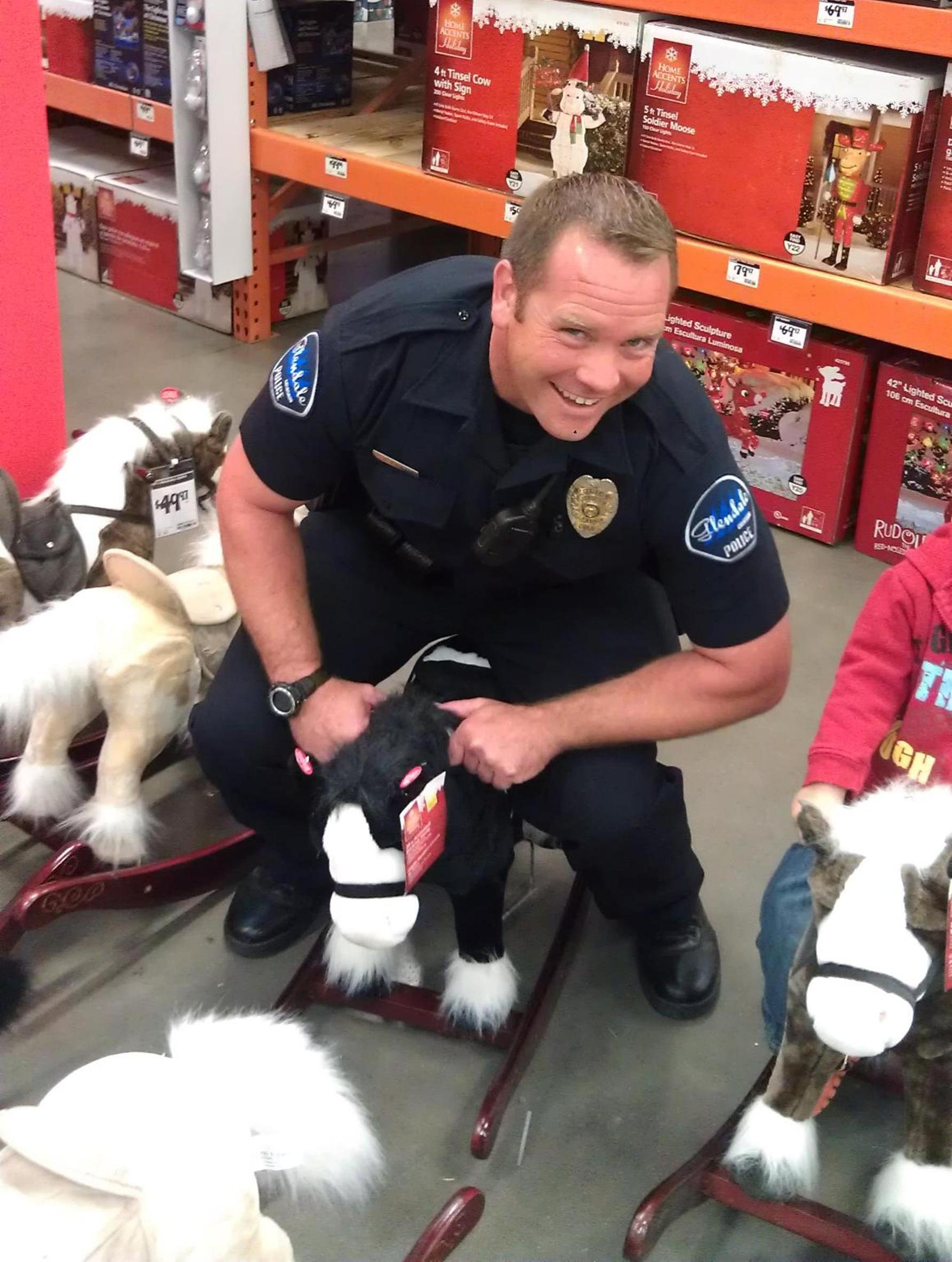 Officer Loar on a children's rocking horse