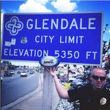 Officer with Rugby ball in front of elevation sign at 5280