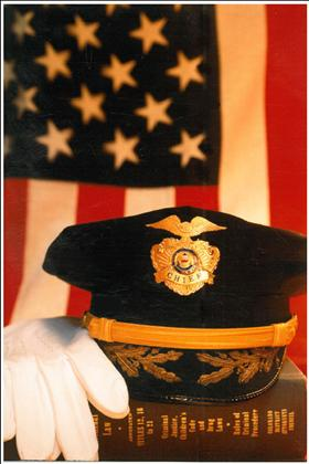 Police Chief's hat and dress gloves in front of flag