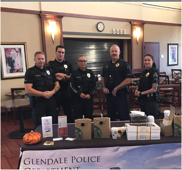 The chief and 4 officers with coffee and donuts, waiting to visit with the public